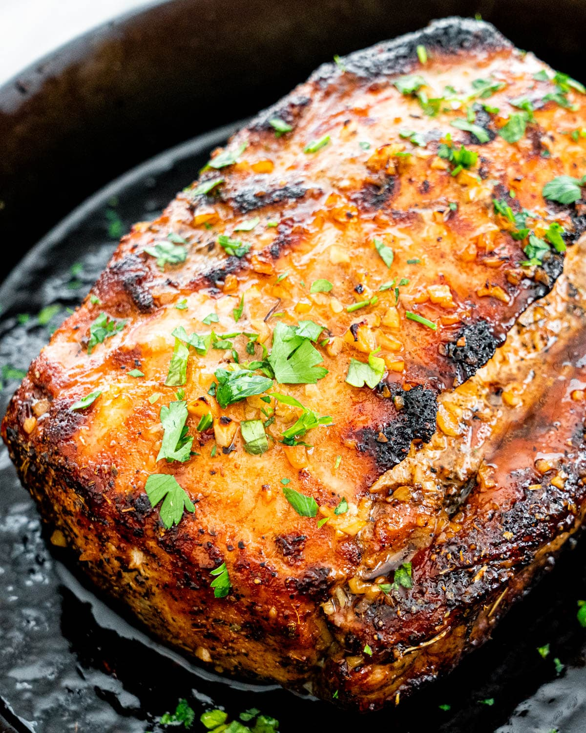 a pork loin glazed with honey garlic sauce in a skillet garnished with parsley
