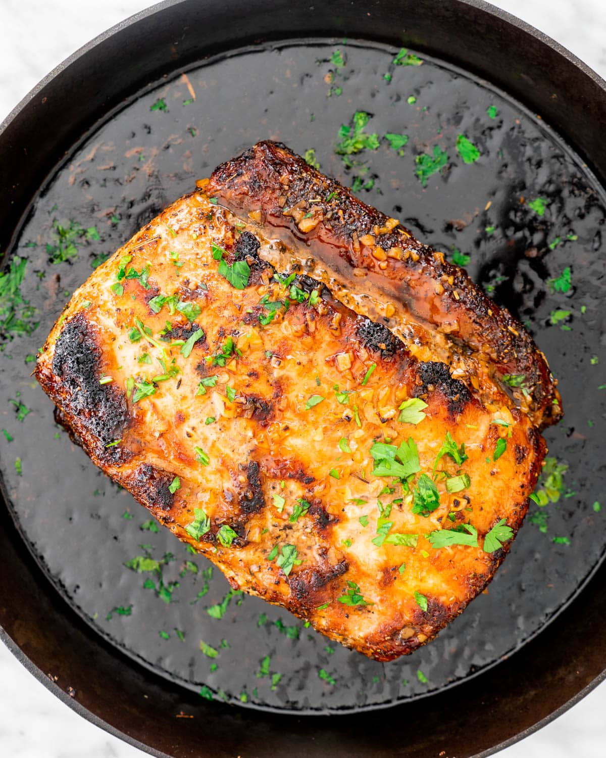 overhead shot of a pork loin roast in a skillet glazed with a honey garlic sauce