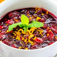 closeup of cranberry sauce in a white bowl garnished with orange zest and mint.