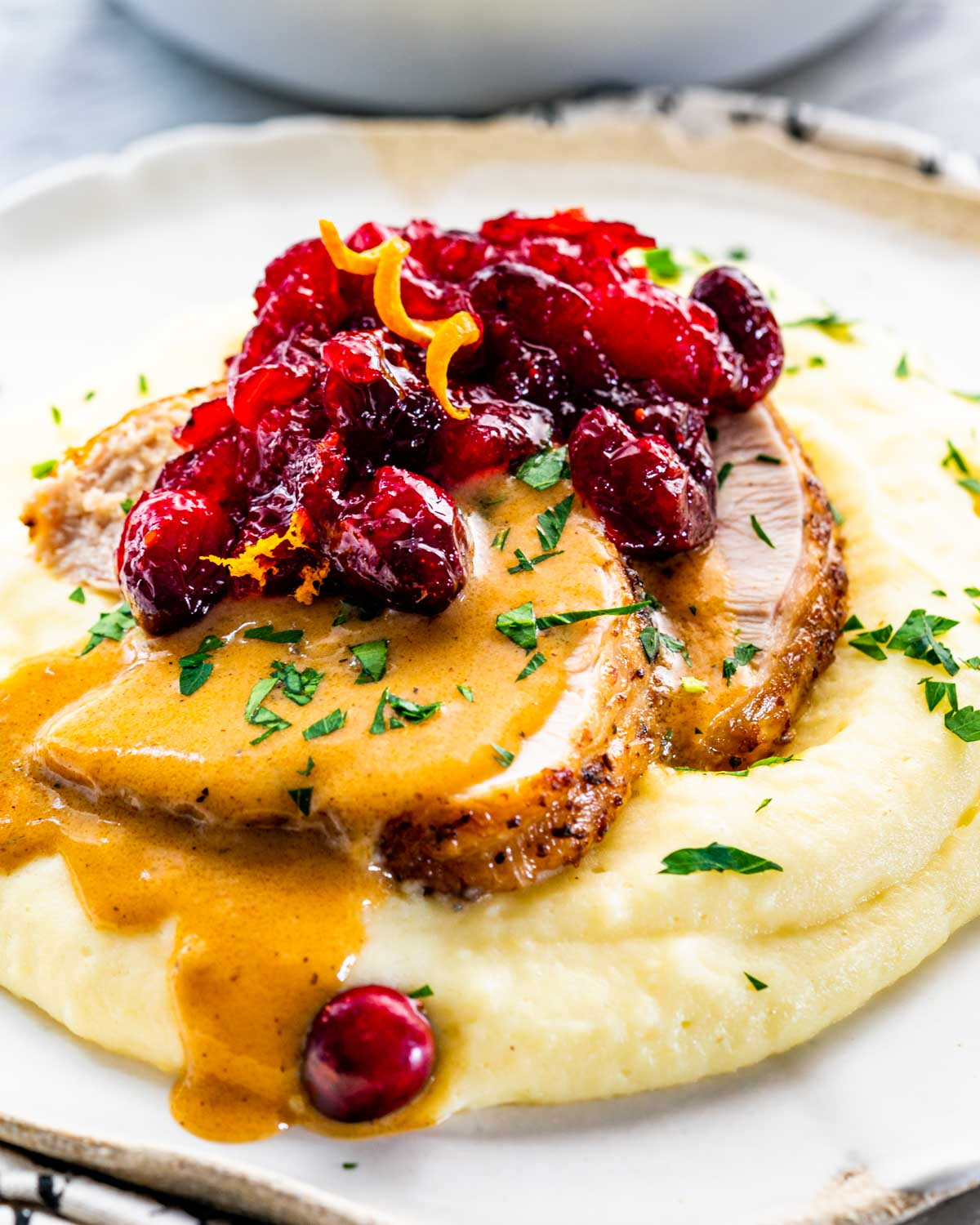 mashed potatoes with 2 slices of turkey breast. gravy and cranberry sauce.