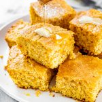 pieces of cornbread stacked on a plate with honey being drizzled over them