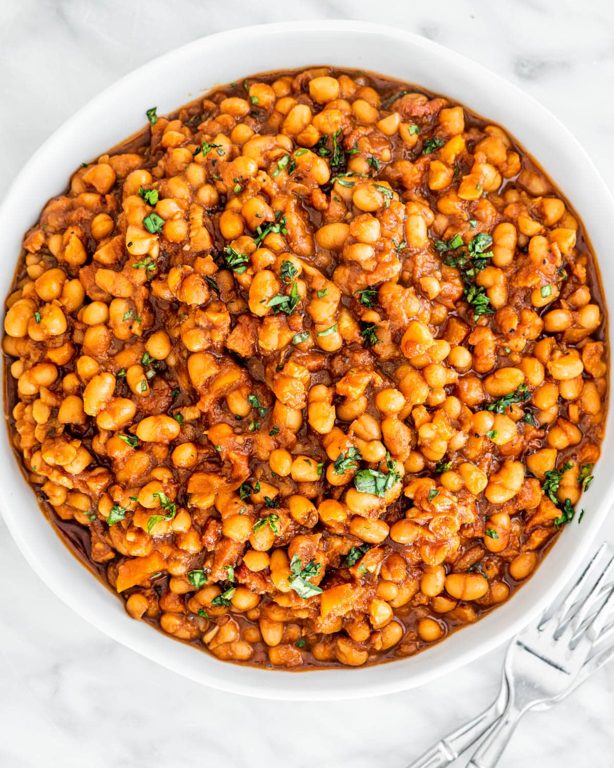 overhead shot of baked beans in a white bowl garnished with parsley