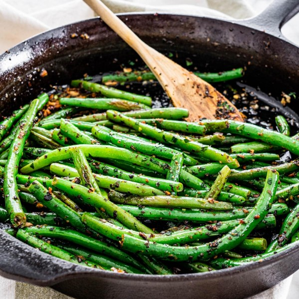 green beans in a skillet with a wooden spoon