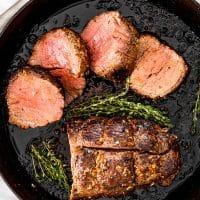 beef tenderloin in a pan with half of it sliced
