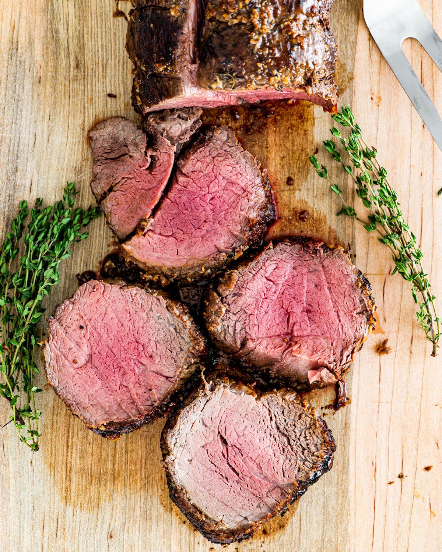 overhead shot of sliced up beef tenderloin on a cutting board