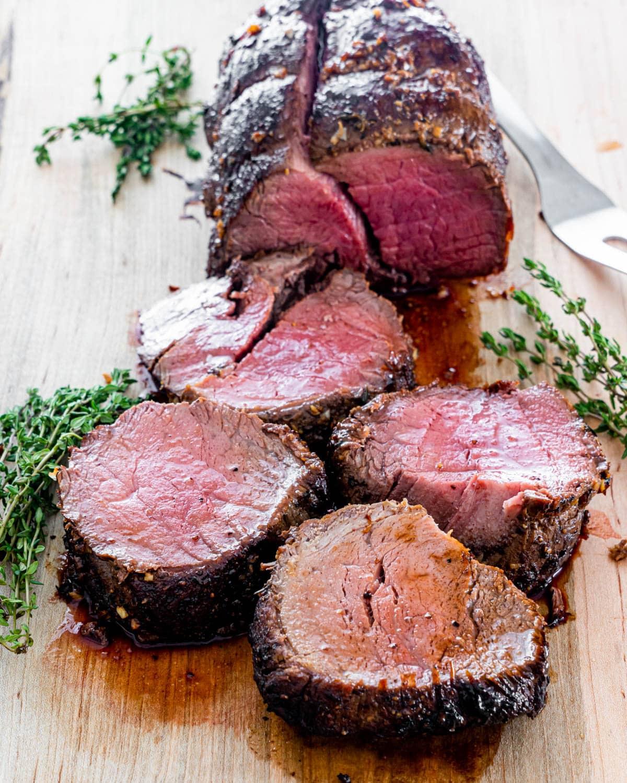 sliced up beef tenderloin on a cutting board