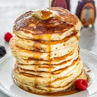 syrup being poured over a stack of buttermilk pancakes