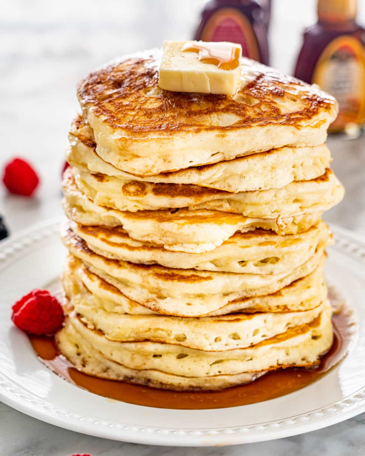 a stack of pancakes topped with butter and maple syrup