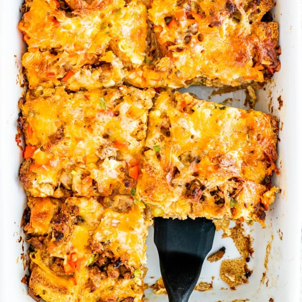 overhead shot of a spatula scooping up a piece of breakfast casserole from the pan