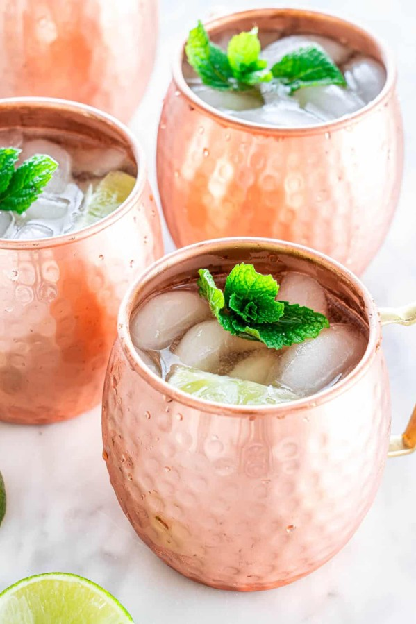 copper mugs filled with moscow mule cocktails topped with sprigs of mint