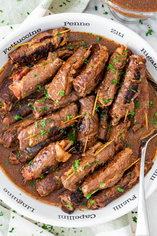 overhead shot of beef rouladen in a large serving bowl with a serving spoon