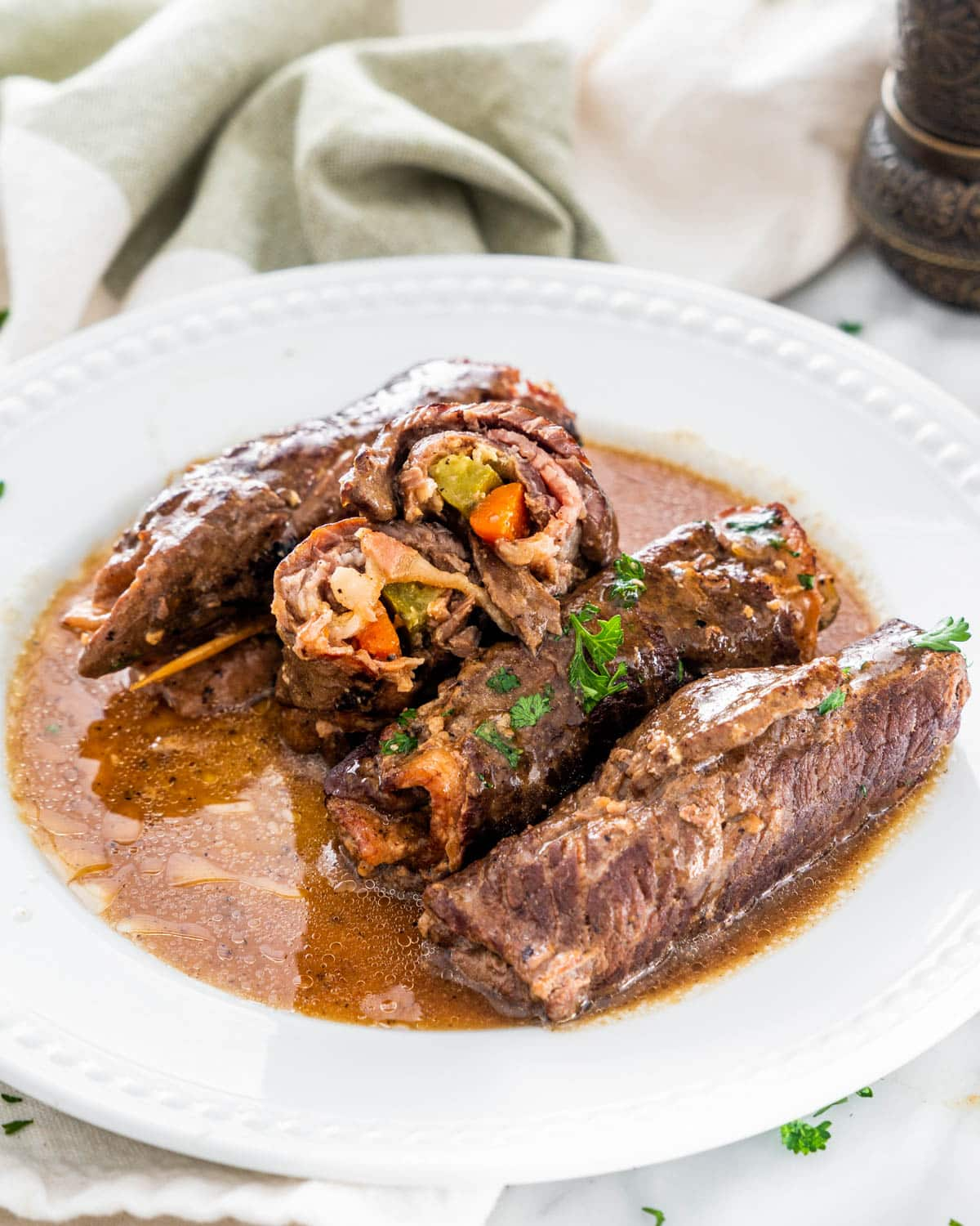 beef rouladen pieces in a white plate with gravy