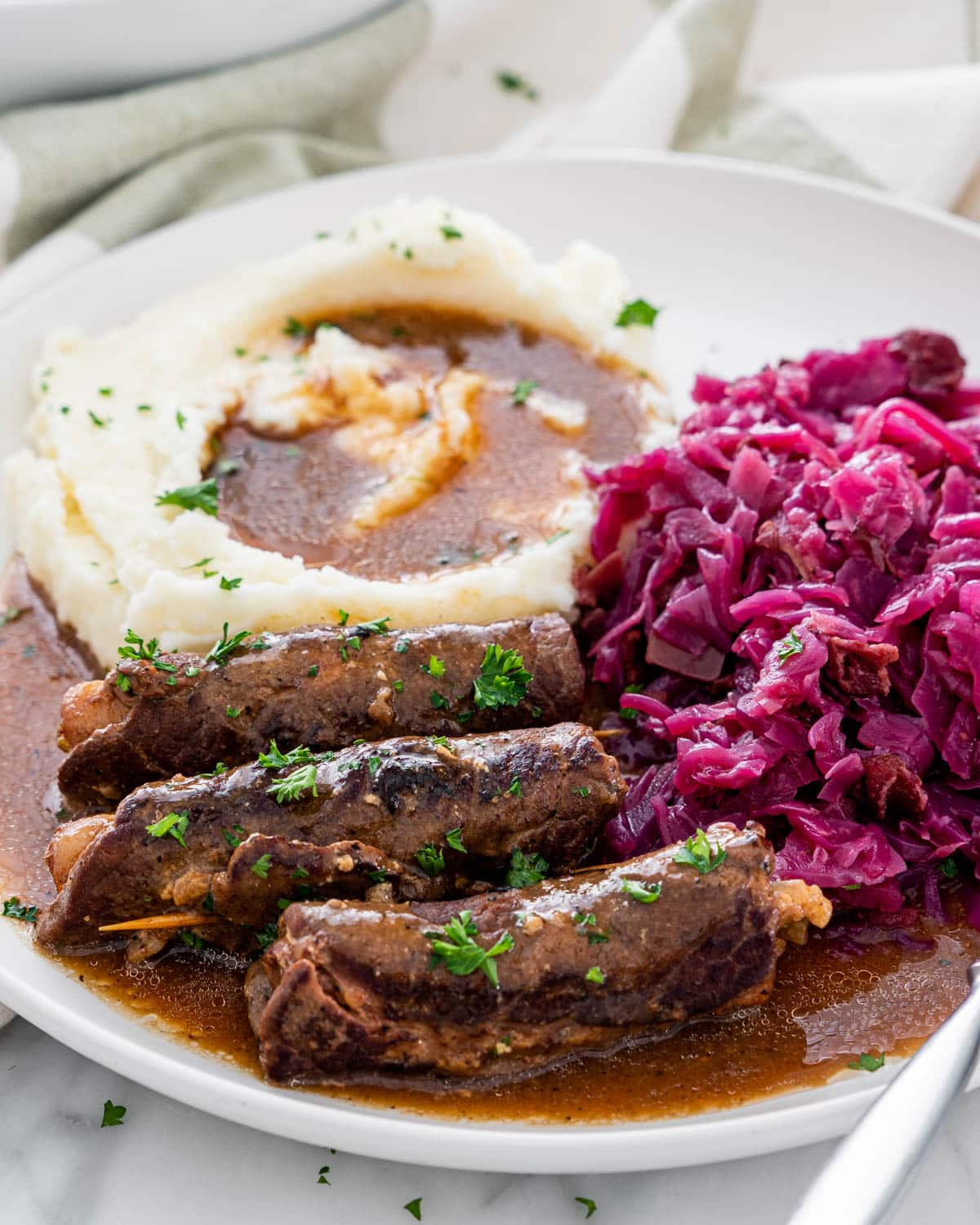 beef rouladen with gravy, mashed potatoes and red cabbage on a white plate