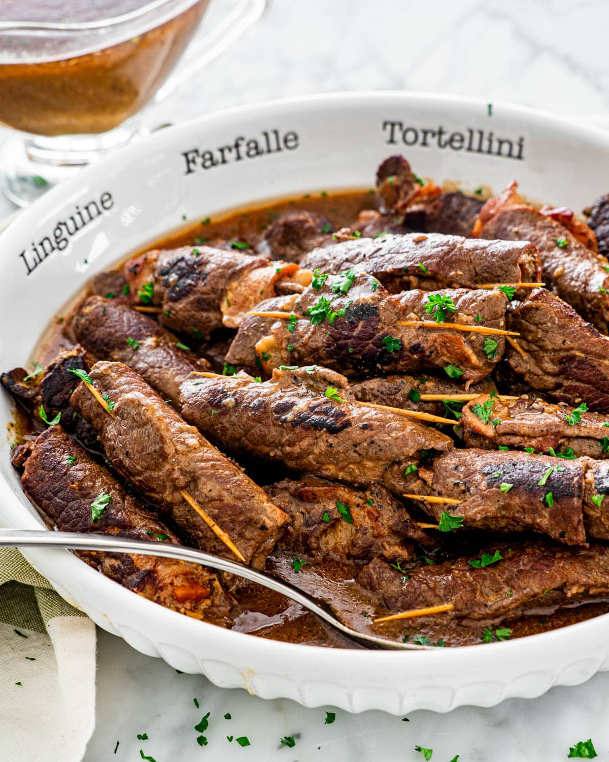 beef rouladen with lots of gravy in a large white bowl