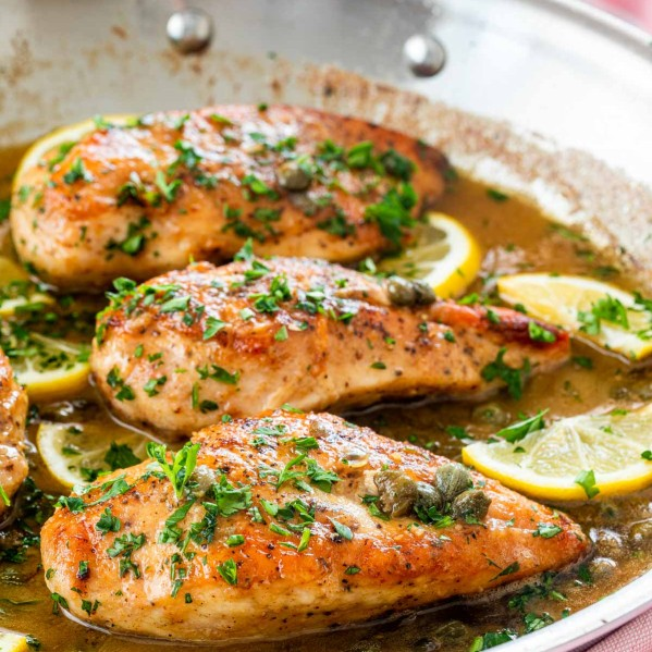 freshly made chicken piccata in a skillet garnished with parsley and lemon wedges.