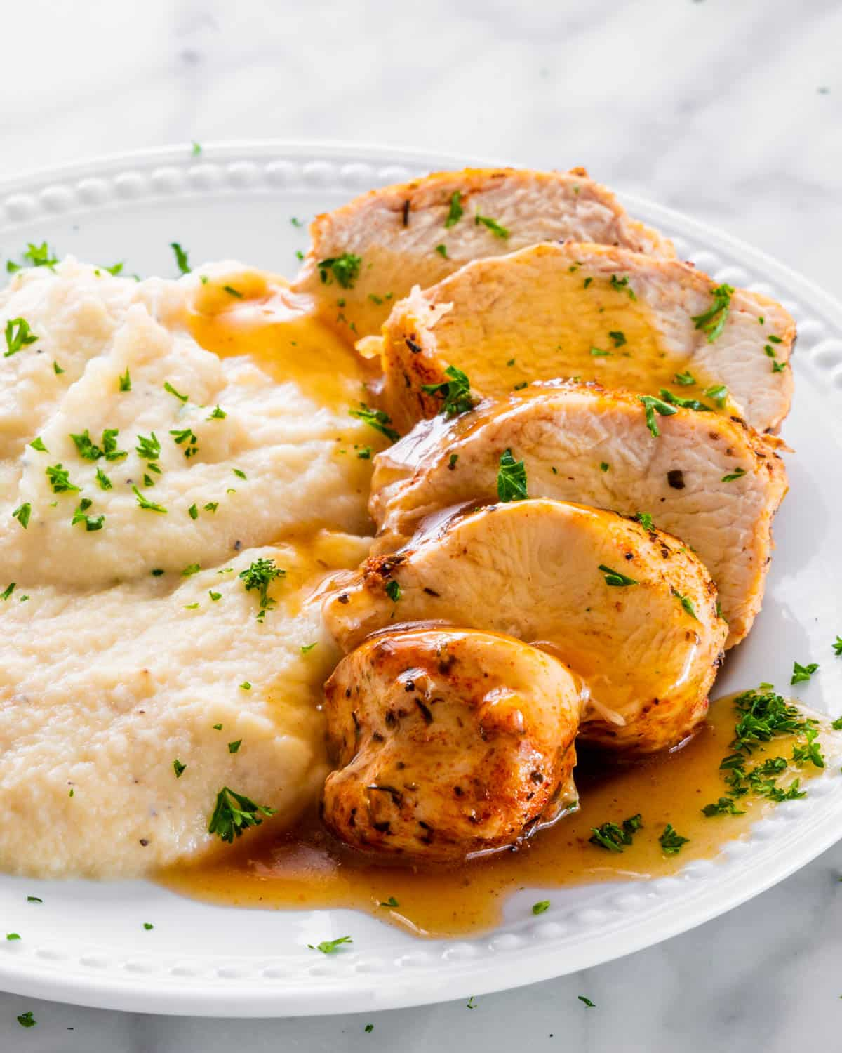 sliced chicken breast with gravy and mashed cauliflower on a white plate