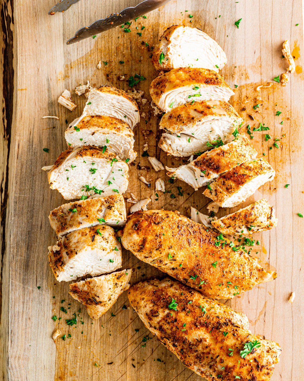 overhead shot of sliced chicken breasts on a cutting board