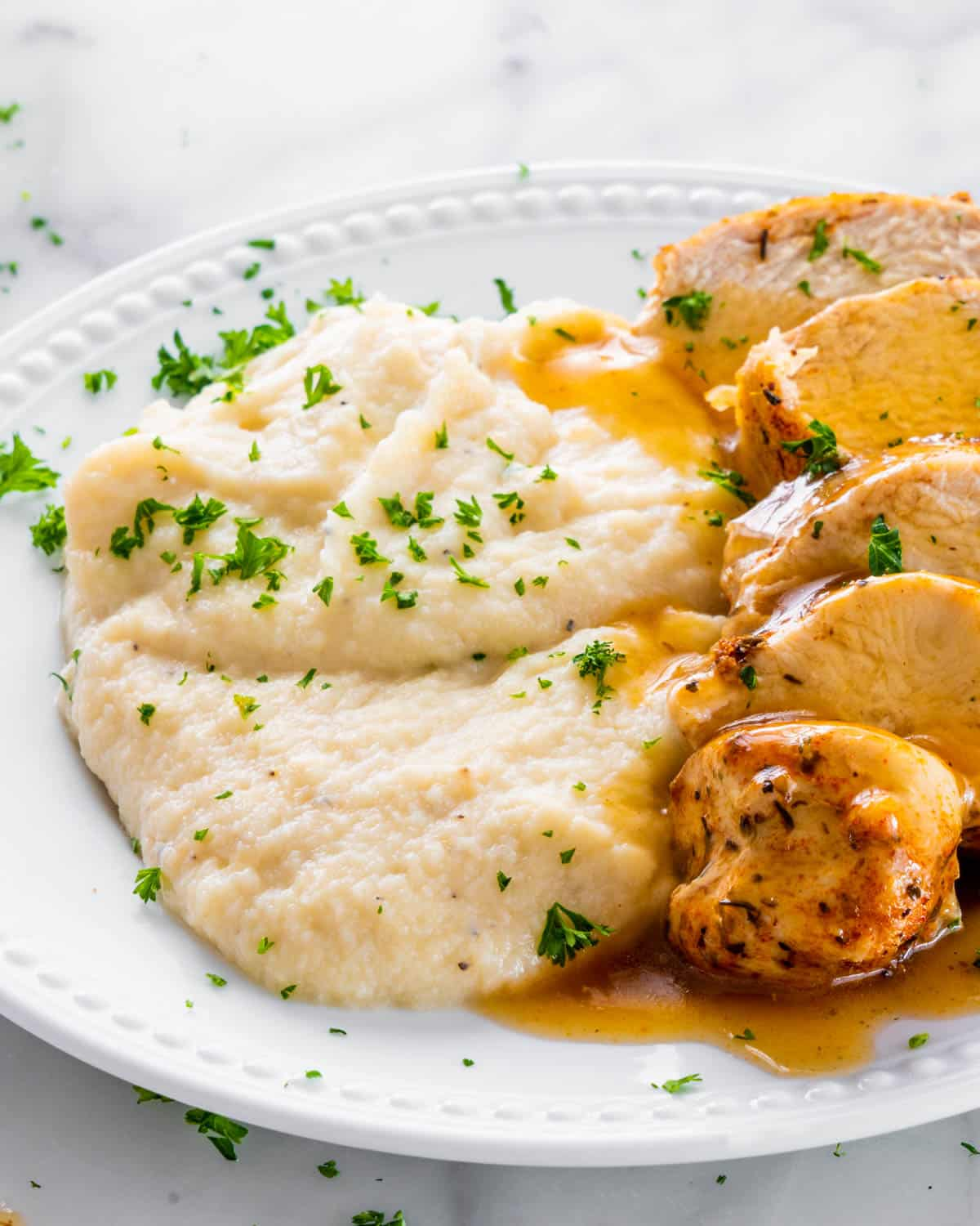 mashed cauliflower with chicken and gravy on a white plate