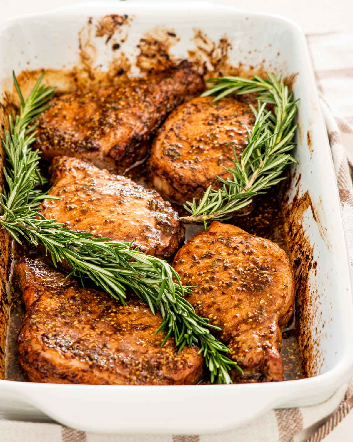 mustard balsamic pork chops in a white casserole dish garnished with rosemary.