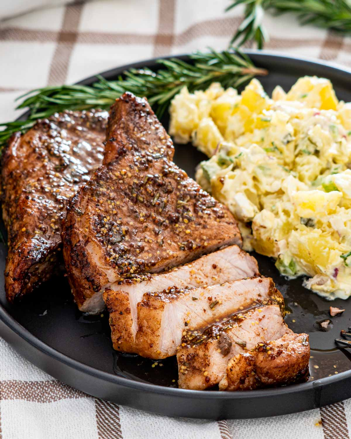 a mustard balsamic pork chop on a black plate sliced up next to potato salad.