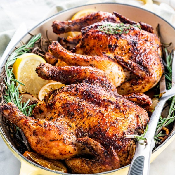 two roasted cornish hens in a roasting pan with sprigs of rosemary and lemon slices