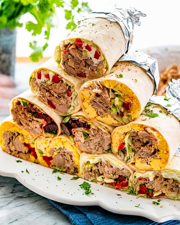 pork carnitas burritos stacked on a serving platter.