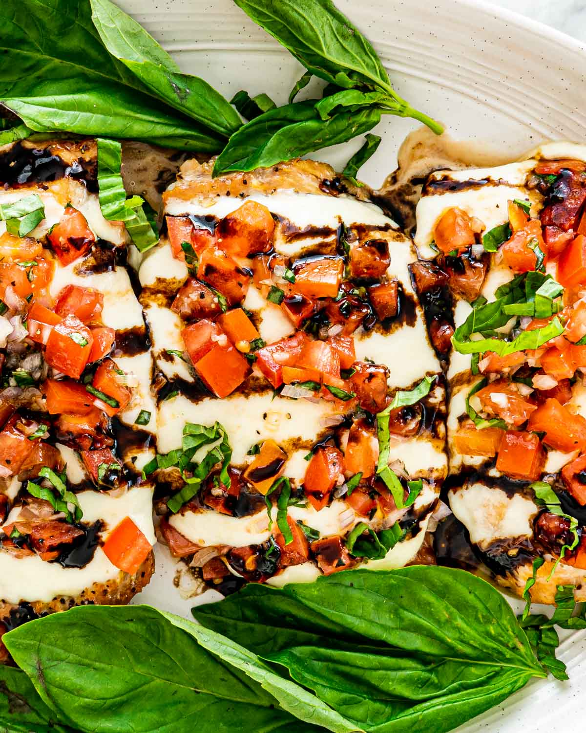 closeup of bruschetta chicken on a platter garnished with basil