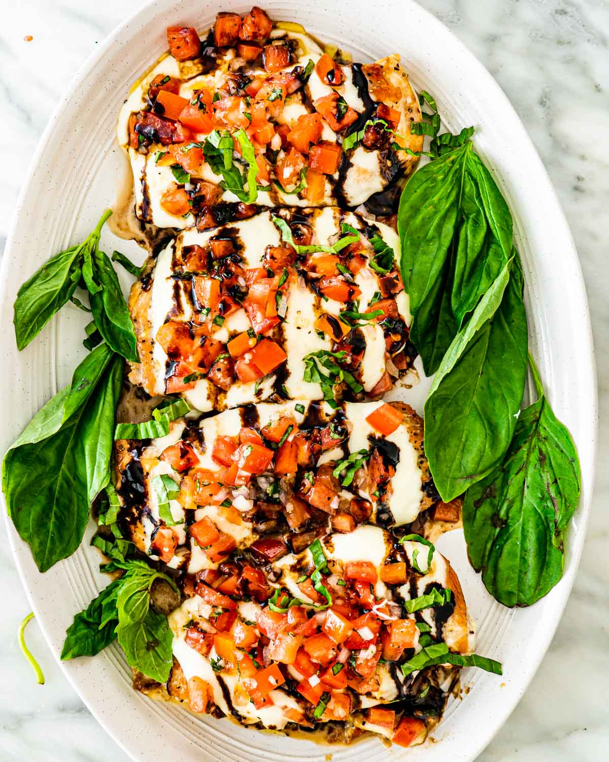 4 pieces of bruschetta chicken on a white serving platter