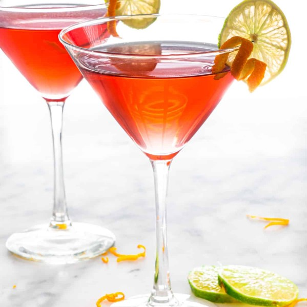 two cosmopolitan cocktails in martini glasses garnished with orange twists and lime slices