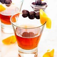 a manhattan drink in a glass garnished with an orange twist and bourbon cherries