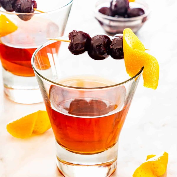 a manhattan drink in a glass garnished with an orange twist and bourbon cherries
