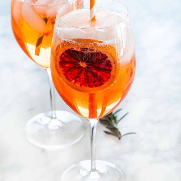 two wine glasses full of aperol spritz garnished with a slice of blood orange and straw