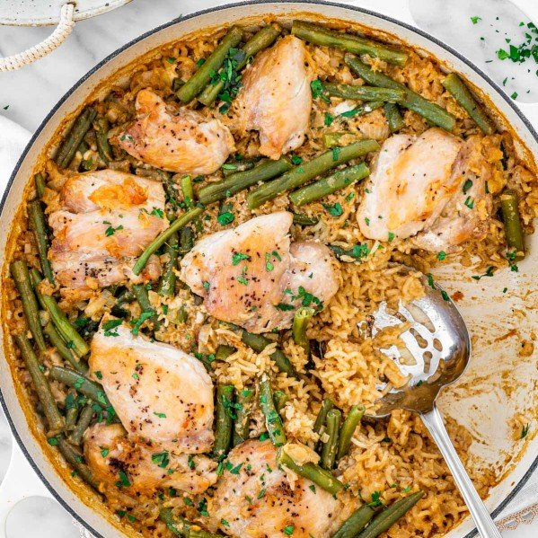 overhead shot of coconut chicken with rice and green beans in a large beige braiser with some rice already taken out and a serving spoon inside