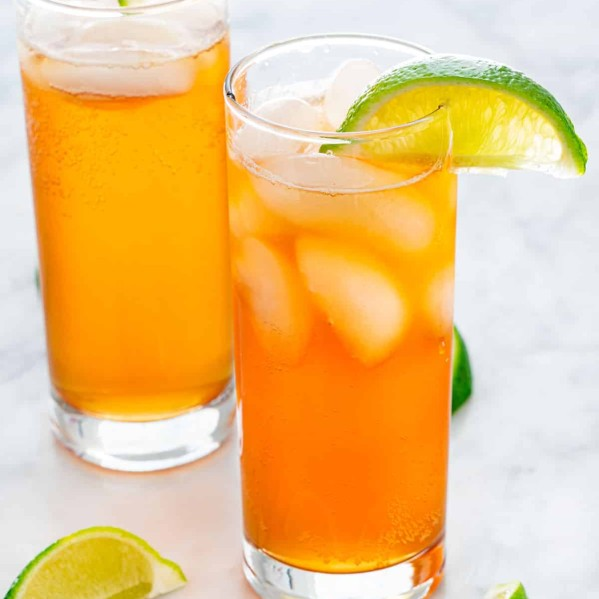 Two dark and stormy cocktails in tall glasses, garnished with lime wedges