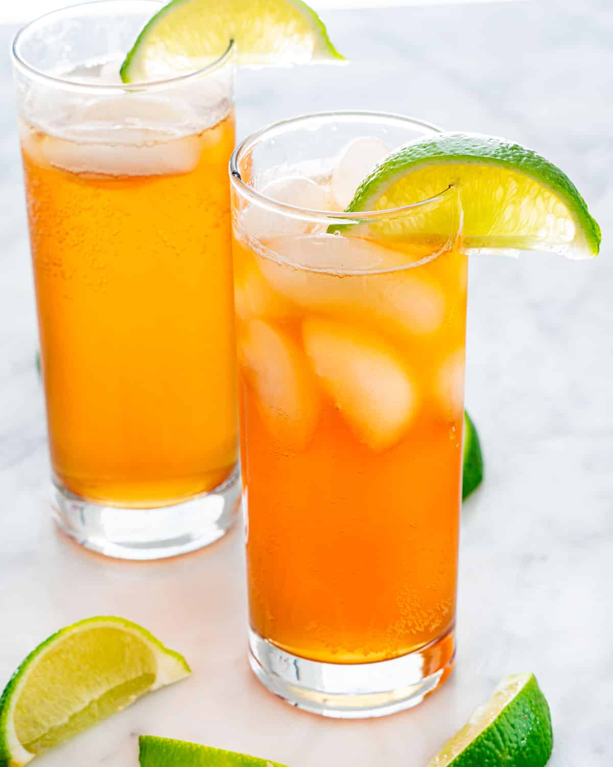 two collins glasses filled with dark and stormy and garnished with a lime wedge