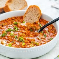 side view shot of a bowl of lentil soup with a piece of bread and a spoon in it