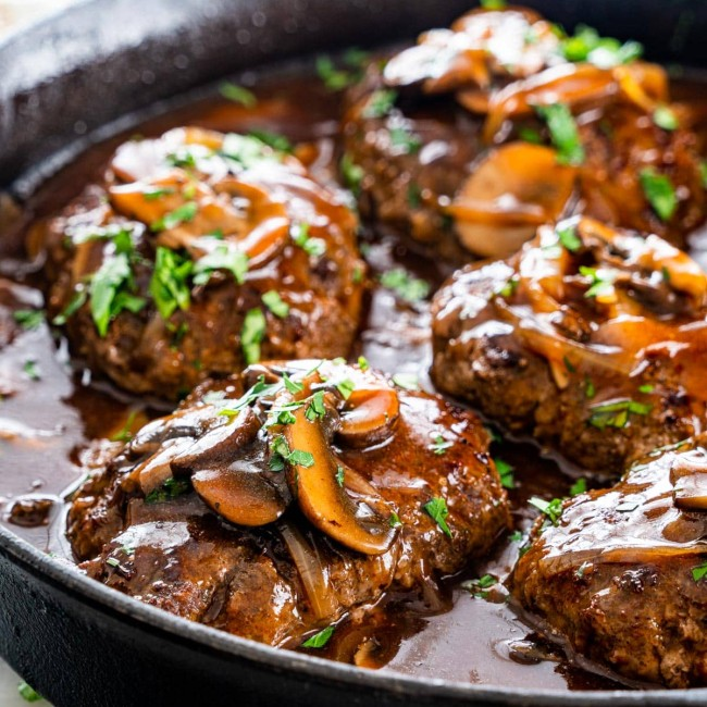 side view shot of salisbury steaks in a skillet, topped with mushrooms, garnished with chopped parsley
