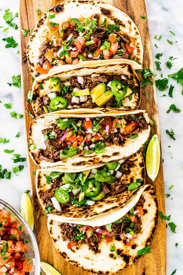 overhead shot of a bunch of tacos on a long cutting board with barbacoa beef, some topped with pico de gallo and some with onion, avocado and jalapeno peppers