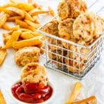 side picture of a basket full of chicken nuggets with a nugget in a small bowl with ketchup and fries in the background