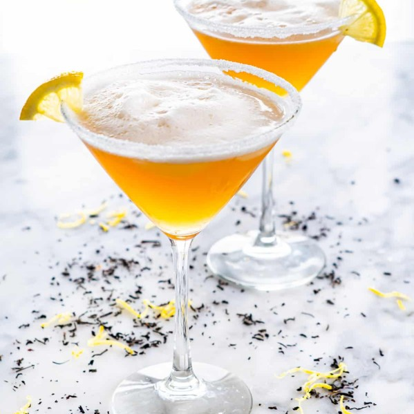 side shot of 2 martini glasses filled with earl grey martini and garnished with lemon wedges
