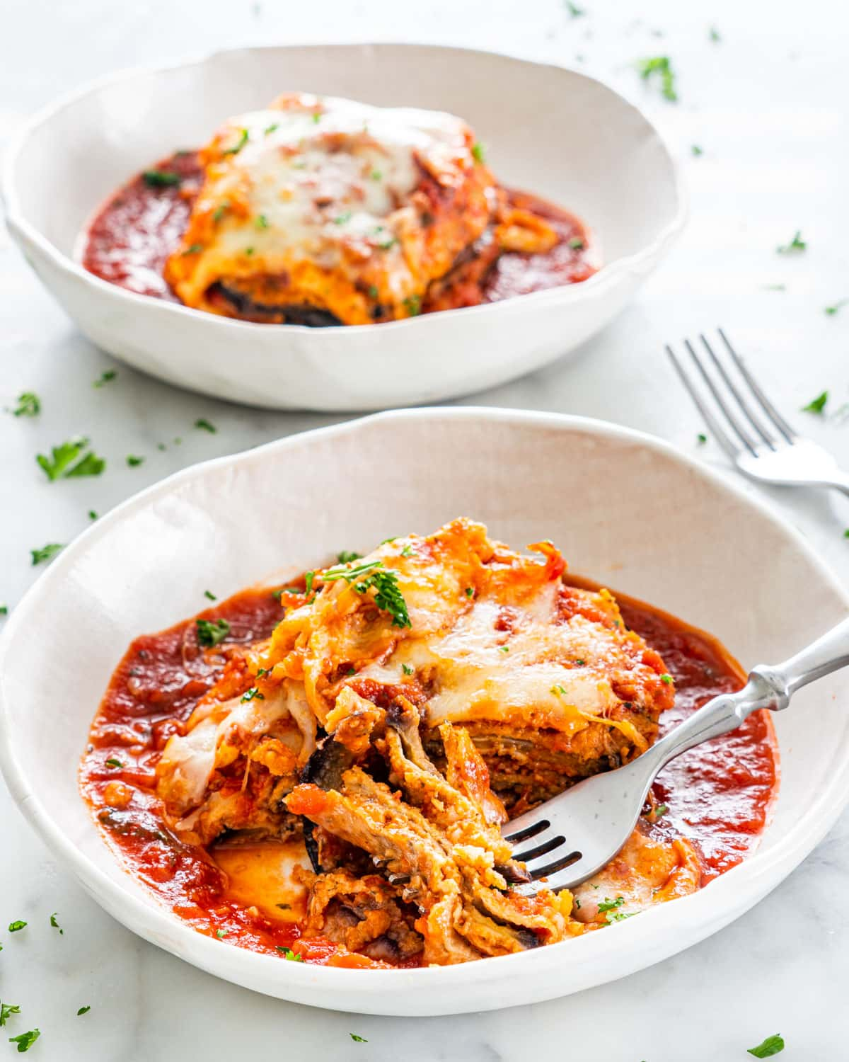 side view shot of a piece of eggplant parmesan with marinara sauce in a white plate garnished with parsley and a piece cut out and held by a fork