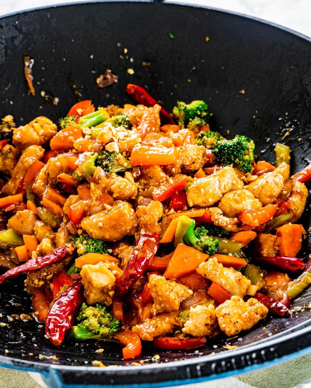 side shot of hunan chicken freshly made in a big blue wok