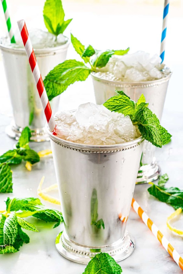 side shot of 3 mint julep cups filled with mint julep, crushed ice and lots of fresh mint