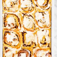 overhead shot of apple pecan cinnamon rolls fresh out of the oven iced with cream cheese icing