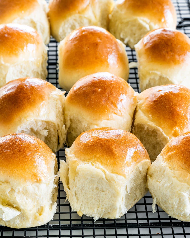 sideview shot of freshly baked dinner rolls on a black cooling rack