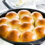 side shot of freshly baked quick yeast dinner rolls in a skillet brushed with butter