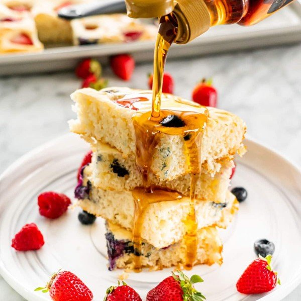 a hand pouring maple syrup over a stack of pancakes surrounded by berries