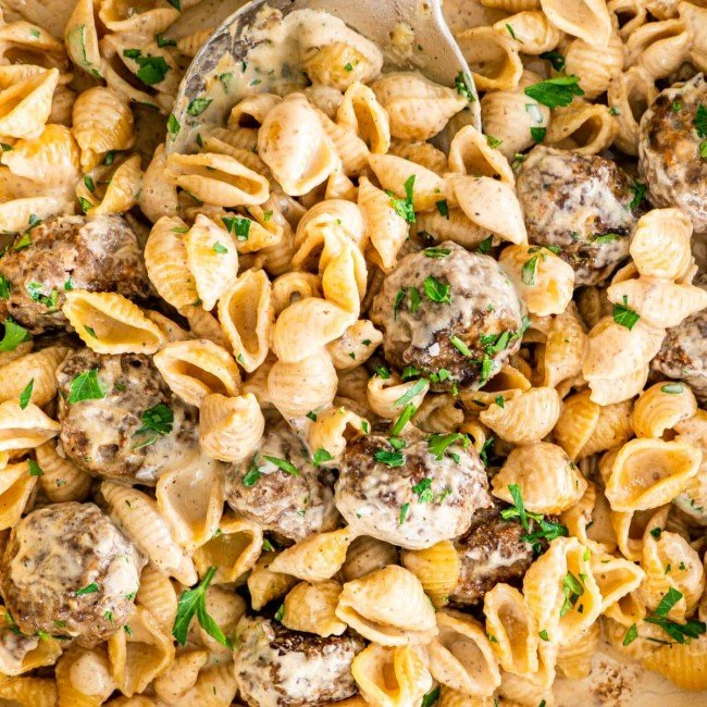 overhead close up shot of swedish meatball pasta in a beige braised garnished with parsley
