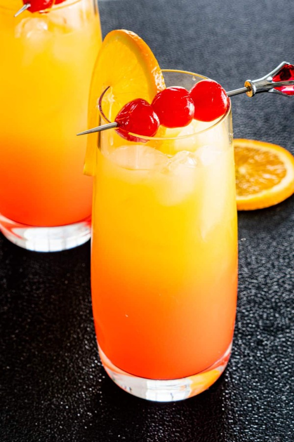 two glasses with tequila sunrise garnished with orange and maraschino cherries