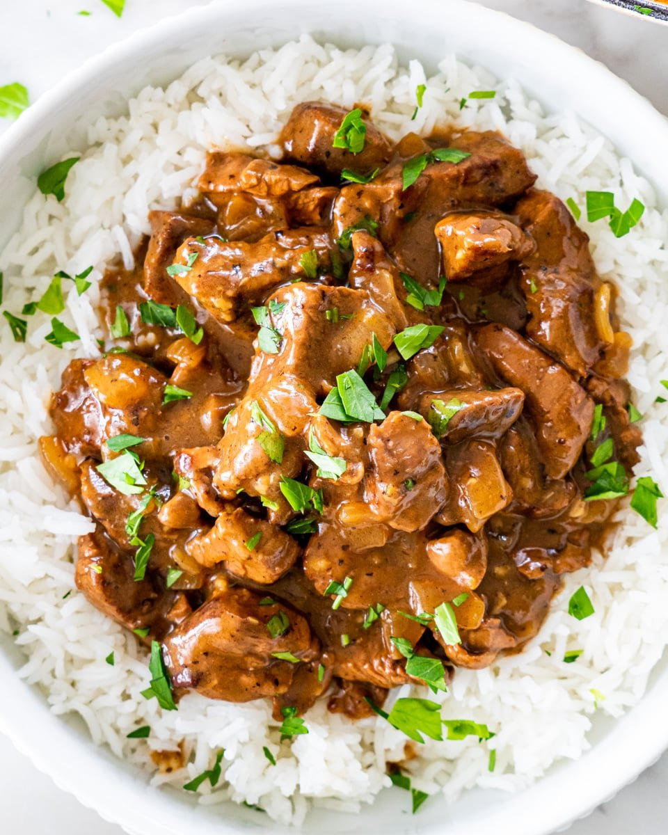 overhead shot of beef tips with gravy over a bed of rice and garnished with parsley
